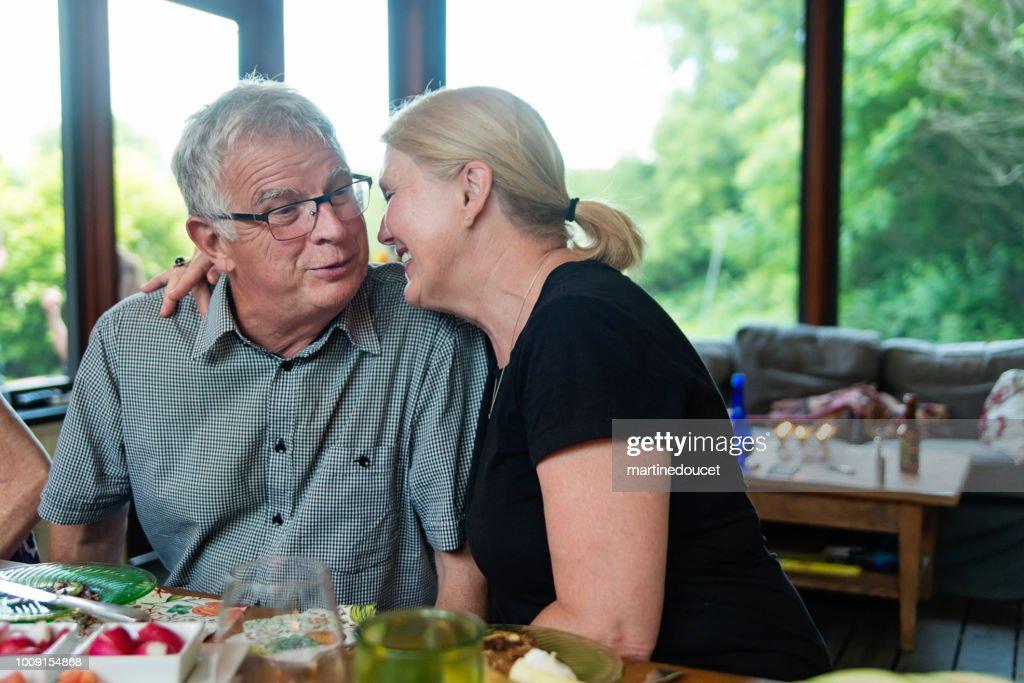 Tender moment for senior couple at dinner in summer house. : Stock Photo