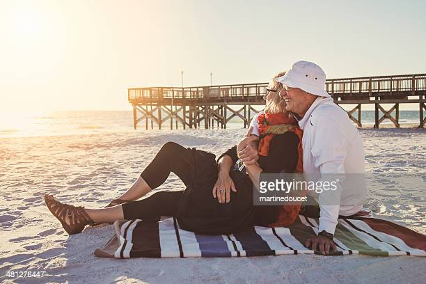 Tender moment for senior couple on the beach at sunset.