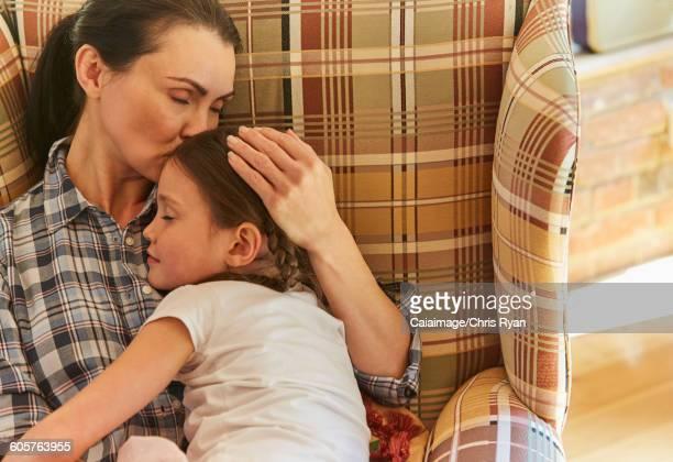 Tender mother cuddling sleeping daughter in armchair