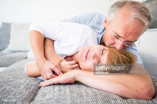 Tender senior couple at home lying on couch