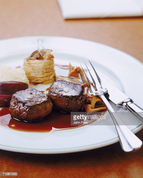 Tenderloin, savory sauce and fork on plate, close-up