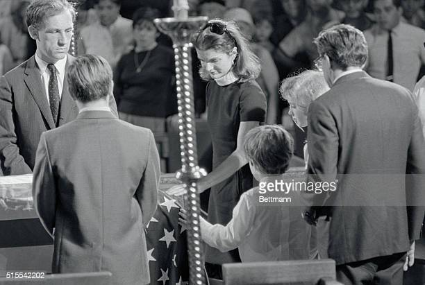 Tenderly placing their hands on the flagdrped casket Mrs Jacqueline Kennedy and her children Caroline and John Jr pray for Senator Robert F Kennedy...