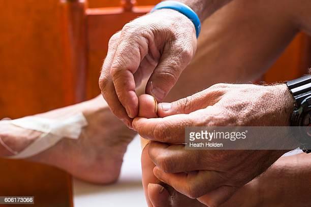 Tending to blisters on feet while running for the 3rd day on September 16 2016 in Kathmandu Nepal Set up by Australian runner Tim Blair the four day...