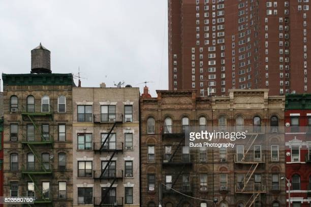tenement houses in chinatown, with tall skyscraper in the background. new york city, usa - lower east side manhattan stockfoto's en -beelden