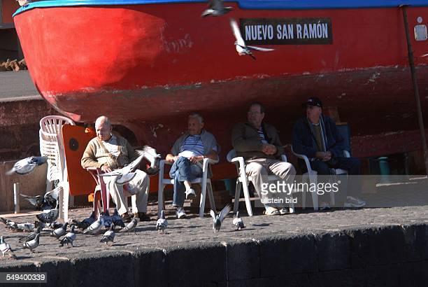 Teneriffa. Puerto de la Cruz, Senioren sitzen im Schatten eines Bootes im alten Fischereihafen