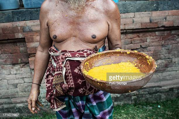 Tenganananese man carries traditional potion made of turmeric and vinegar to heal the wounds of the fighters during the Pandanus War ritual on June...
