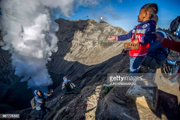 A Tengger tribe boy throws small change into the crater of Bromo volcano as an offering in Probolinggo East Java province on June 30 as part of...