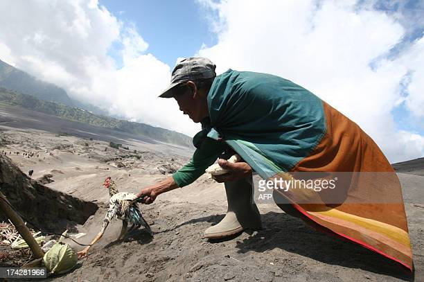 Tengger tribe devotees belonging to Indonesia's Hindu minority prepare to throw a chicken offering to the active crater of Mount Bromo volcano in...