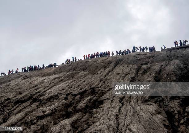 Tengger tribe members and local tourists climb the summit of Mount Bromo volcano to throw offerings such as livestock or banknotes into the crater in...