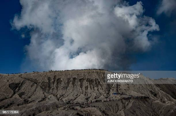 TOPSHOT Tengger tribe people and tourists climb the summit of Bromo volcano to throw offerings into the crater in Probolinggo East Java province on...