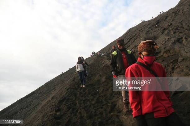 Tengger tribe people make their way to the summit of Mount Bromo volcano to make offerings in Probolinggo, East Java province, Indonesia on July 7 as...