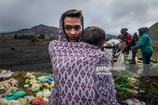 Tenggerese carries his brother after praying at a temple before going to mount Bromo during the Yadnya Kasada Festival at the crater of Mount Bromo...
