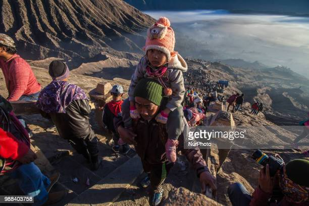 Tenggerese carrying his child while climbing Mount Bromo during the ceremony of Yadnya Kasada Festival at Probolinggo East Java on 30th April 2018...