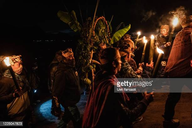Tenggerese hold torches as they carry vegetables known as 'Ongkek' for an offering during the Yadnya Kasada Festival at the crater of Mount Bromo...