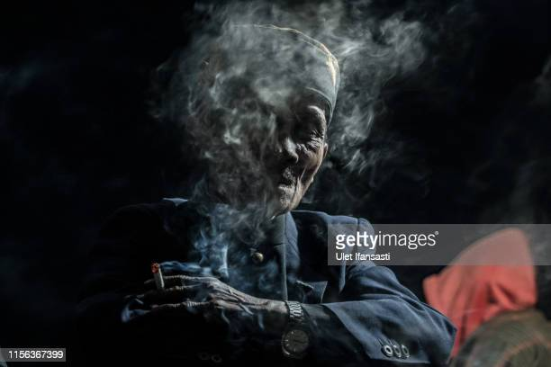 Tenggerese shaman smokes at Poten temple during the Yadnya Kasada Festival at crater of Mount Bromo on July 18 2019 in Probolinggo Java Indonesia...