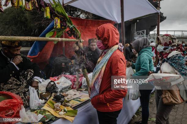 Tenggerese wear protective masks as they praying at Poten temple before going to Mount Bromo during the Yadnya Kasada Festival at the crater of Mount...