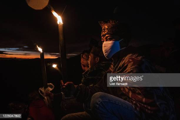 Tenggerese wears a mask hold a torch during the Yadnya Kasada Festival at the crater of Mount Bromo amid the coronavirus pandemic on July 07, 2020 in...
