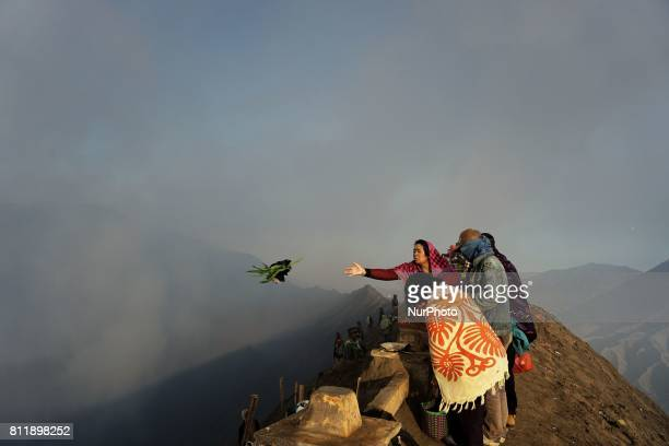 Tenggerese worshipper throws offerings during the Yadnya Kasada Festival at crater of Mount Bromo in Probolinggo East Java Indonesia Yadnya Kasada...