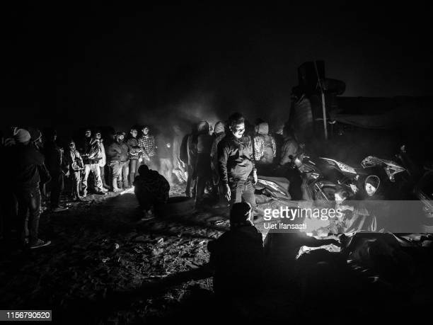 Tenggerese worshippers gather around a fire during the Yadnya Kasada Festival at crater of Mount Bromo on July 18 2019 in Probolinggo Java Indonesia...