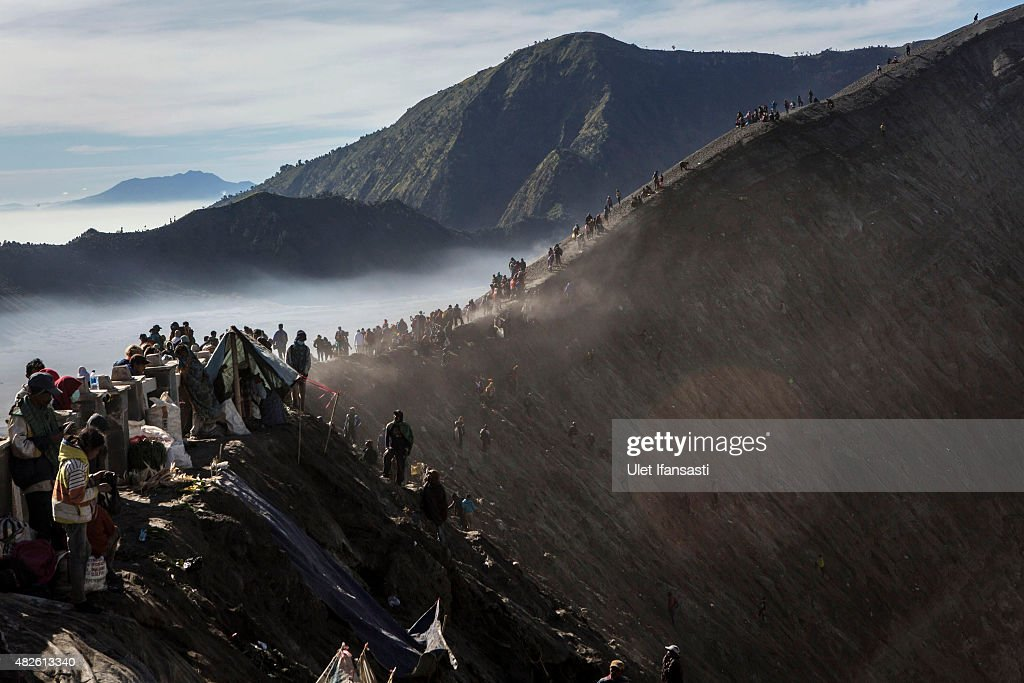 Tenggerese worshippers gather at the crater of Mount Bromo during the Yadnya Kasada Festival on August 01, 2015 in Probolinggo, East Java, Indonesia. The festival is the main festival of the Tenggerese people and lasts about a month. On the fourteenth day, the Tenggerese make the journey to Mount Bromo to make offerings of rice, fruits, vegetables, flowers and livestock to the mountain gods by throwing them into the volcano's caldera. The origin of the festival lies in the 15th century when a princess named Roro Anteng started the principality of Tengger with her husband Joko Seger, and the childless couple asked the mountain Gods for help in bearing children. The legend says the Gods granted them 24 children but on the provision that the 25th must be tossed into the volcano in sacrifice. The 25th child, Kesuma, was finally sacrificed in this way after initial refusal, and the tradition of throwing sacrifices into the caldera to appease the mountain Gods continues today.