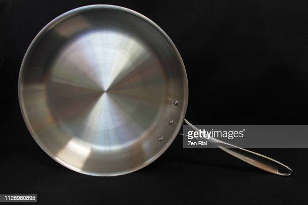 a ten-inch stainless steel frying pan on black background - cooking pan stock pictures, royalty-free photos & images