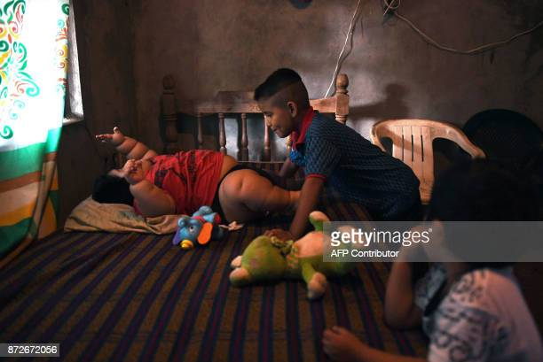 Tenmonthold Luis Gonzales is pictured with his cousin Michel and his brother Mario at his home in Tecoman Colima state Mexico on November 8 2017 Luis...