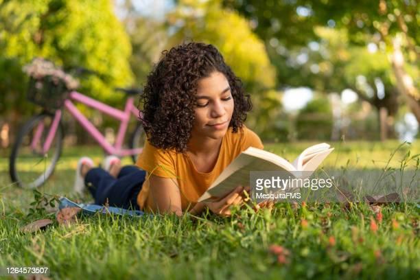 tenn flicka läser en bok som ligger på gräset - litteratur bildbanksfoton och bilder