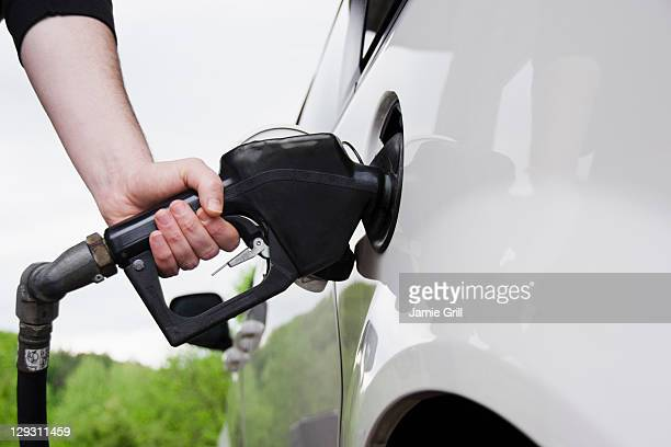 USA, Tennessee, Memphis, Close up of man's hand holding fuel pump and refueling car