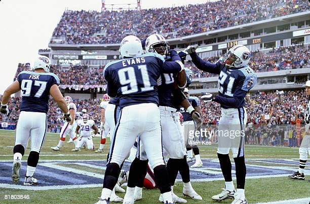 Tennessee Titans defensive tackle Josh Evans and cornerback Samari Rolle celebrate with defensive end Jevon Kearse after he sacks the quarterback in...