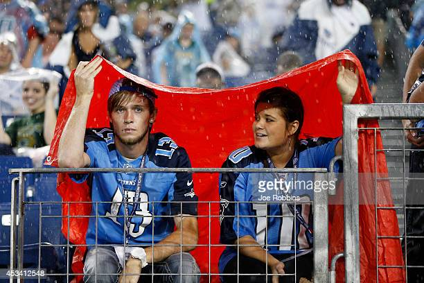 Tennessee Titans fans try to keep dry during a rainstorm in the second quarter of an NFL preseason game against the Green Bay Packers at LP Field on...