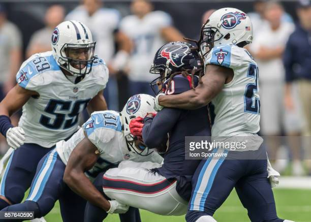 Tennessee Titans free safety Kevin Byard and Tennessee Titans cornerback Brice McCain tackle Houston Texans wide receiver DeAndre Hopkins during the...