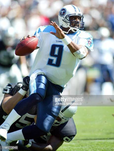 Tennessee Titans' quarterback Steve McNair tries to elude a sack from Oakland Raiders' defensive end Chris Cooper and Raiders' defensive tackle Sam...