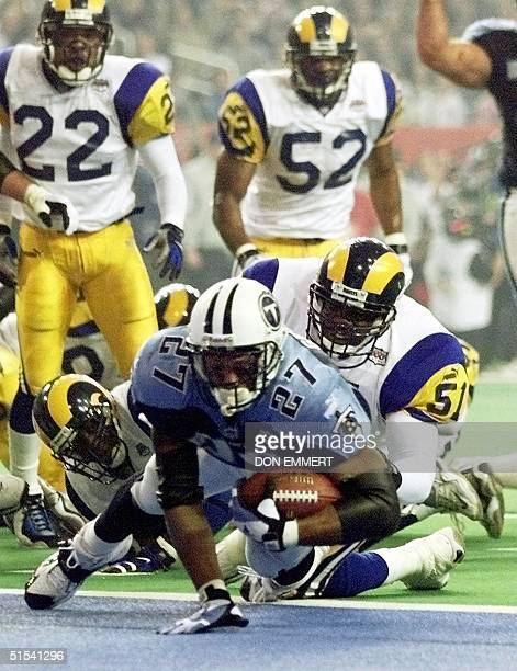Tennessee Titans running back Eddie George dives into the end zone for a touchdown as St Louis Rams linebacker Lorenzo Styles attempts to stop him...