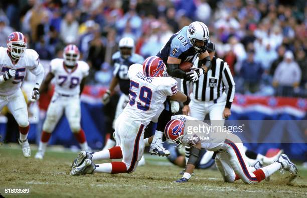 Tennessee Titans tight end Frank Wycheck is brought down by Buffalo Bills linebacker Sam Rogers and safety Henry Jones during the AFC Wildcard...