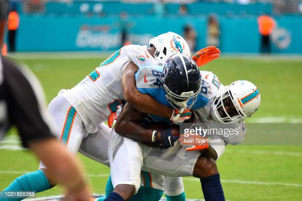 Tennessee Titans Wide Receiver Corey Davis gets tackled by Miami Dolphins Linebacker Raekwon McMillan left and Miami Dolphins Safety Reshad Jones...