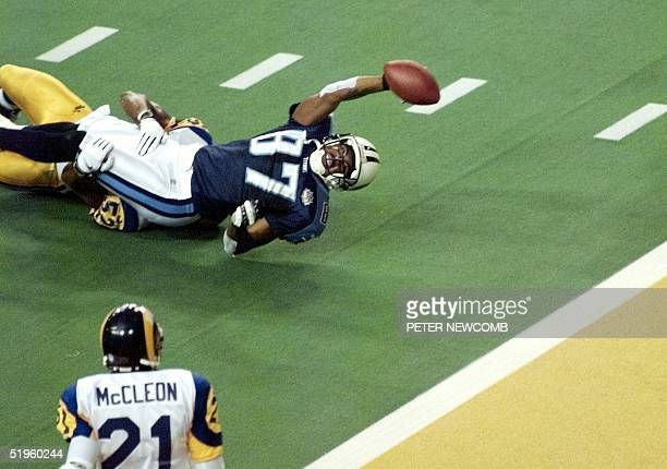 Tennessee Titans wide receiver Kevin Dyson stretches for the end zone but falls short as he is tackled by St Louis Rams linebacker Mike Jones as time...