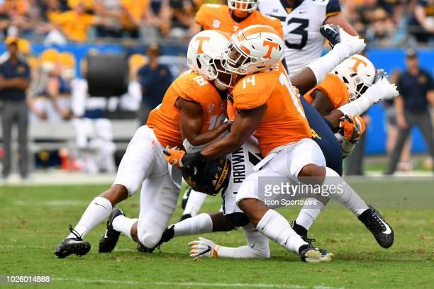 Tennessee Volunteers defensive back Nigel Warrior and Tennessee Volunteers quarterback Zac Jancek collide on the tackle of West Virginia Mountaineers...