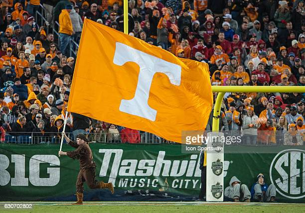 Tennessee's mascot runs the 'Power T' flag across the end zone after a touchdown during the Music City Bowl between the Tennessee Volunteers and...