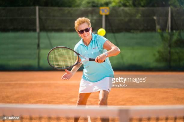 tennis - 70 jaar oude passen senior vrouw tennissen - 70 79 jaar stockfoto's en -beelden