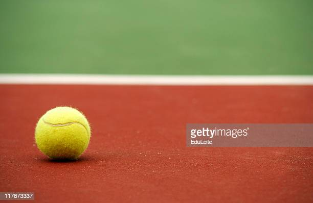 A tennis ball alone on a court background