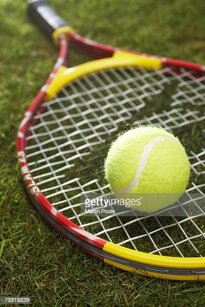 Tennis ball and racket in grass, close up
