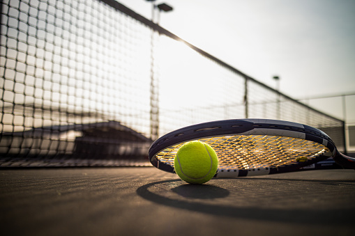 Tennis ball and racket on hard court under sunlight 832170050
