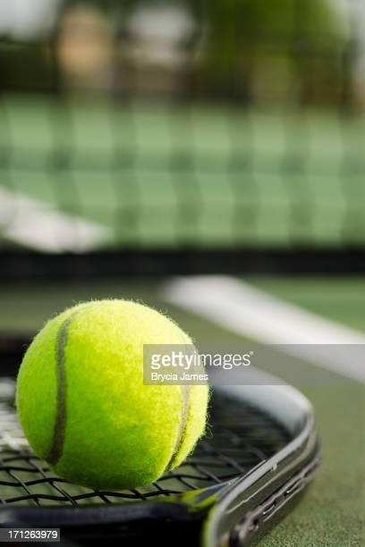 Tennisball und Schläger auf dem Tennisplatz Vertikal