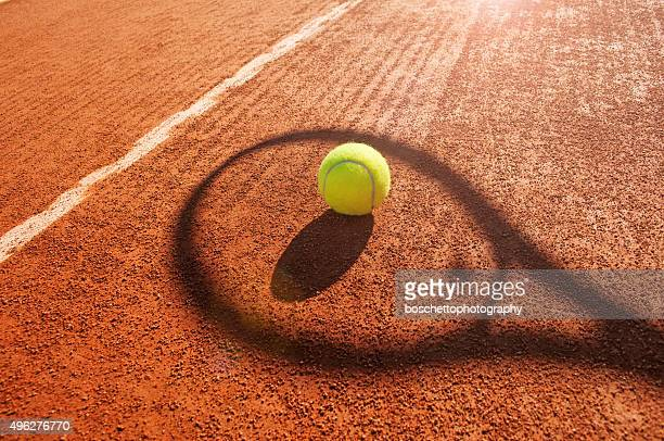 tennis ball and racket shadow on  clay court - tennis stock pictures, royalty-free photos & images