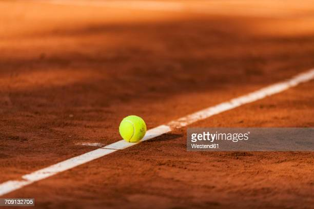 tennis ball hitting the line on clay court - tenista fotografías e imágenes de stock