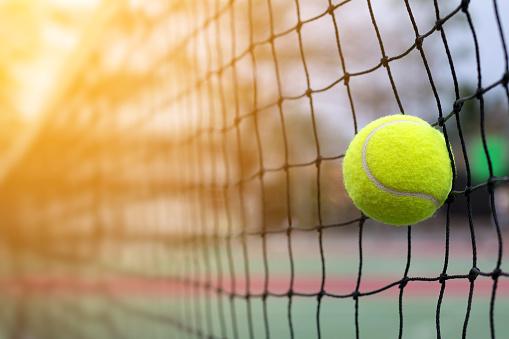 Tennis ball hitting to net on blur court background 914370940
