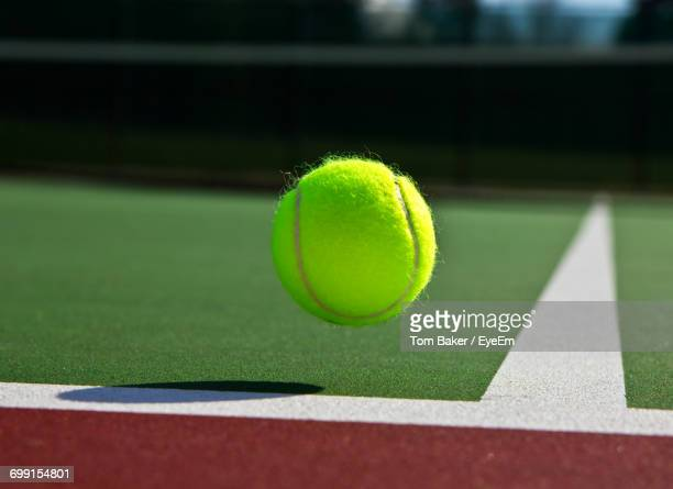 tennis ball in mid-air over corner marking at court - tennis ball stock pictures, royalty-free photos & images