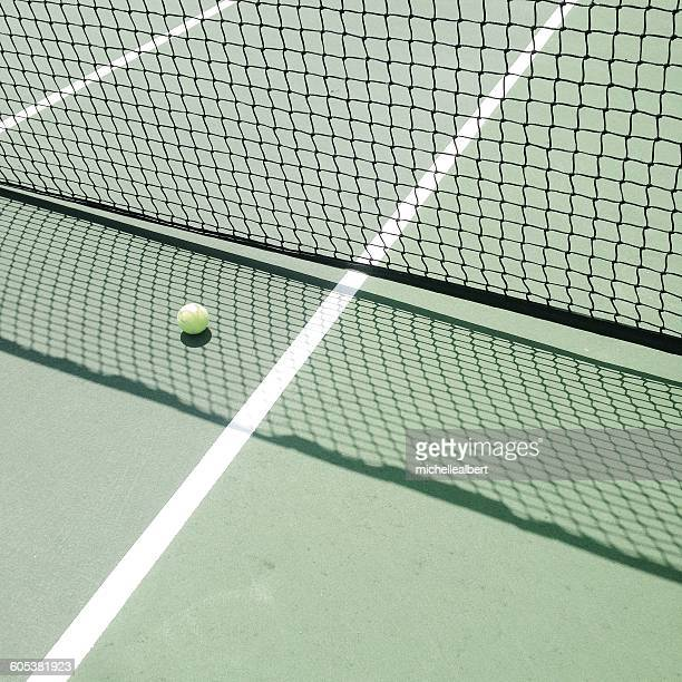 Tennis ball on tennis court in shadow of net