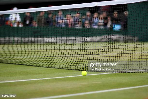 A tennis ball on the grass near the net on an outer court during the Wimbledon Lawn Tennis Championships at the All England Lawn Tennis and Croquet...