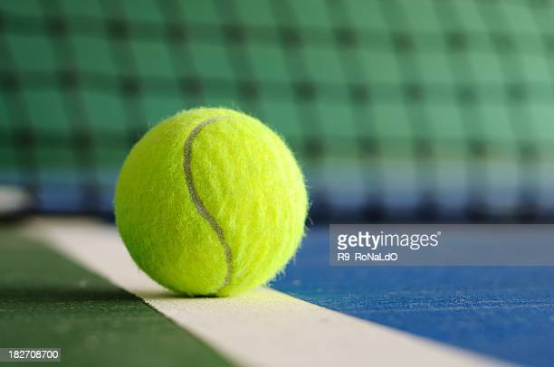 tennis ball on the line with net in background - tennis ball stock pictures, royalty-free photos & images